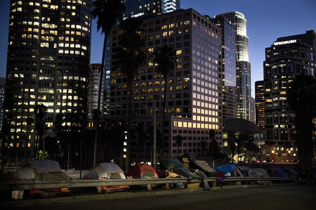 "Homeless tents are dwarfed by skyscrapers as 63-year-old Vincent, who only gave his first name, sorts his belongings Friday, December 1, 2017, in Los Angeles. Vincent said he thought he was bulletproof and never had to worry about getting a job as a young man. ""Things ain't the way they were anymore"". (Photo by Jae C. Hong/AP Photo)"
