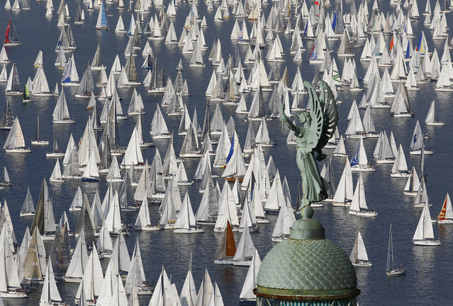 Sailing boats gather at the start of the Barcolana regatta in front of Trieste harbour October 12, 2014. The annual Barcolana regatta in the Gulf of Trieste near northern Italy is one of the largest sailing races in the world with over 1,800 participants. The race began in 1969 and takes place on the second Sunday in October. (Photo by Stefano Rellandini/Reuters)