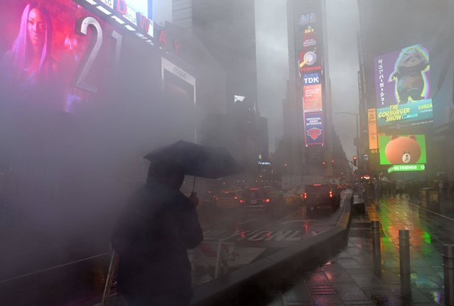A person walks through Times Square in the early morning rain, as heavy storms are expected to hit the area on April 6, 2017 in New York. (Photo by Timothy A. Clary/AFP Photo)