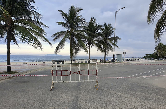 Entrance to a beach is cordoned off following a lockdown order in Da Nang, Vietnam, on Tuesday, July 28, 2020. Vietnam on Tuesday locked down its third-largest city for two weeks after more than a dozen cases of COVID-19 were found in a hospital. (Photo by Luke Groves/AP Photo)