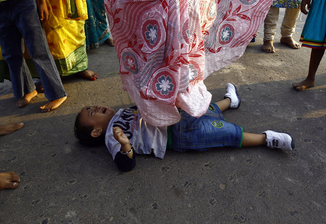 A Hindu woman steps over a child in a ritual seeking blessings for the child from the Sun god Surya during the Chatt Puja festival in Kolkata October 29, 2014. (Photo by Rupak De Chowdhuri/Reuters)