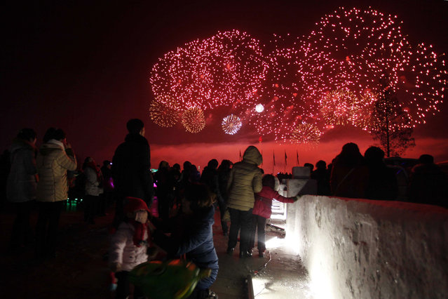 North Koreans watch as fireworks explode as part of New Year celebrations, above the Taedong River as viewed from Kim Il Sung Square, in Pyongyang, North Korea on December 31, 2017. (Photo by Jon Chol Jin/AP Photo)