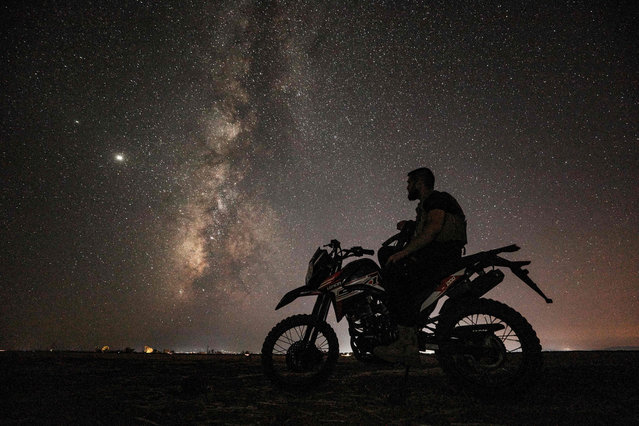 This long-exposure picture taken early on July 23, 2020, shows the Milky Way galaxy rising in the sky above a Syrian fighter of the Turkish-backed National Front for Liberation group on a motorcycle in the town of Taftanaz along the frontlines in the country's rebel-held northwestern Idlib province. (Photo by Omar Haj Kadour/AFP Photo)