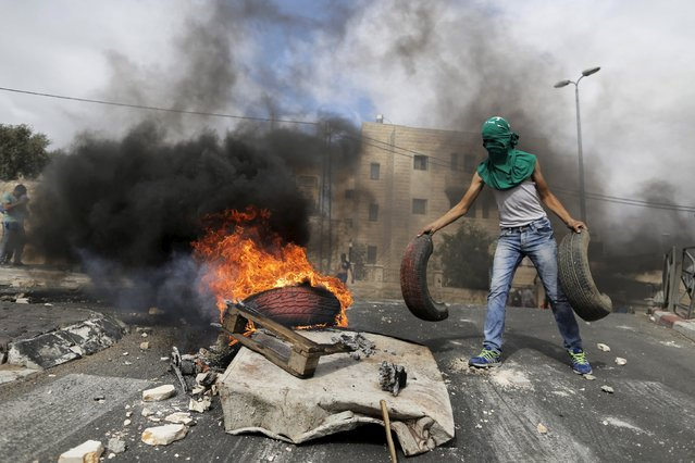 A masked Palestinian youth adds tyres to a fire during clashes with Israeli police in Sur Baher, a village in the suburbs of Arab east Jerusalem, October 7, 2015. A suspected Palestinian militant stabbed and wounded an Israeli soldier, snatched his gun and was then shot dead by special forces on Wednesday, police said, as a surge of violence prompted Israel's prime minister to cancel a visit to Germany. (Photo by Ammar Awad/Reuters)