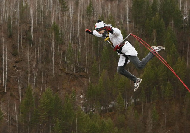 """A member of the amateur rope-jumping group """"Exit Point"""" jumps from a 44-metre high (144-ft) water pipe bridge in the Siberian Taiga area outside Krasnoyarsk, November 2, 2014. (Photo by Ilya Naymushin/Reuters)"""