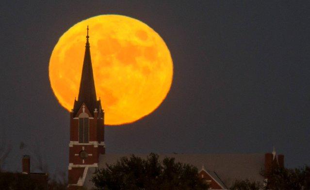 A full moon rises behind St. Joseph Ost Catholic Church in rural Reno County, Kan on Thursday, November 6, 2014. (Photo by Travis Heying/AP Photo/The Wichita Eagle)
