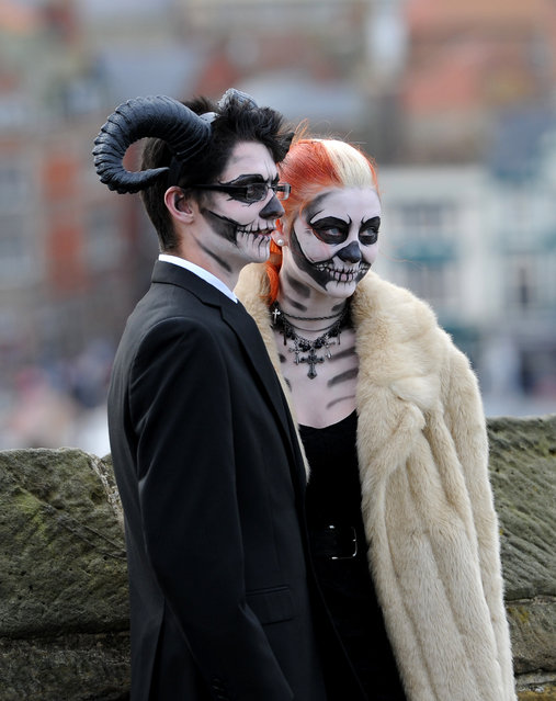 "A couple pose for photographers in the grounds of St Mary's Church during the ""Whitby Goth Weekend"", North Yorkshire, on November 2, 2014. (Photo by Anna Gowthorpe/PA Wire)"