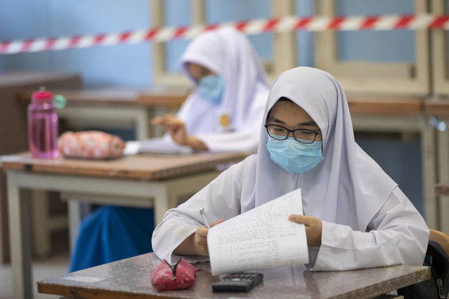 Students wearing face masks and maintaining social distancing at a classroom during the first day of school reopening at a high school in Putrajaya, Malaysia, Wednesday, June 24, 2020. Malaysia began reopening schools Wednesday while entering the Recovery Movement Control Order (RMCO) after three months of coronavirus restrictions. (Photo by Vincent Thian/AP Photo)