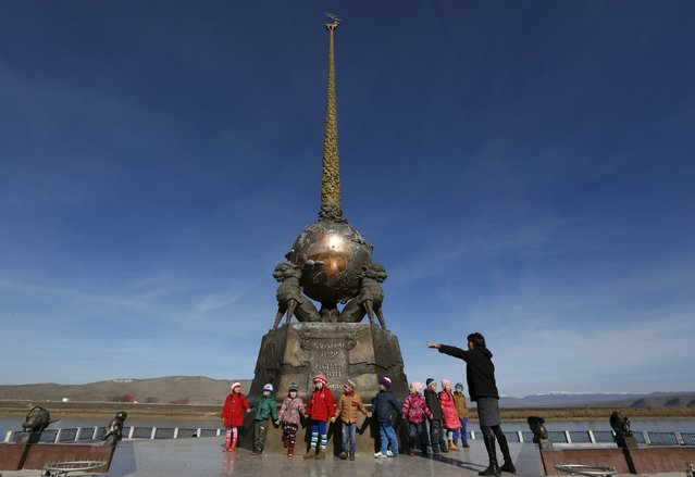 """Pupils and a teacher gather on an embankment of the Yenisei River near """"The Centre of Asia"""" cast bronze sculpture by Russian Buryat artist Dashi Namdakov in the town of Kyzyl, administrative centre of Tuva region, Southern Siberia, Russia, October 11, 2015. (Photo by Ilya Naymushin/Reuters)"""