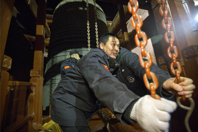 Security officials ring the bell at midnight to mark the arrival of the Lunar New Year at the Bell Tower in Beijing, Friday, February 16, 2018. (Photo by Mark Schiefelbein/AP Photo)