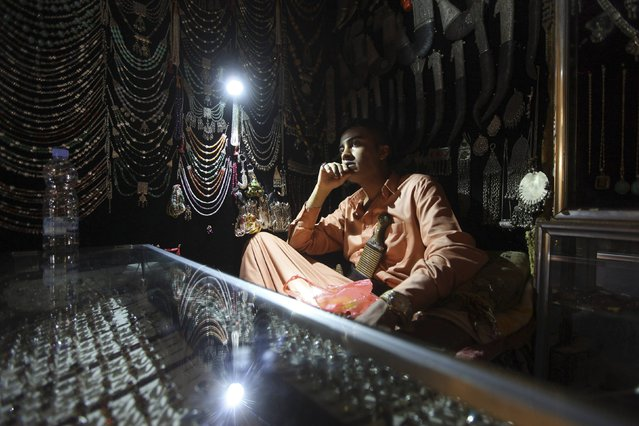 A silverware vendor sits by the light of a lamp as he waits for customers in his shop at a marketplace in the Old City of Sanaa November 23, 2014. Yemen suffers from a shortage of electric power as exposed electrical lines are frequently attacked by tribesmen. (Photo by Mohamed al-Sayaghi/Reuters)