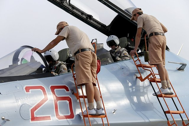 Russian ground staff members check on a Sukhoi Su-30 fighter jet at the Hmeymim air base near Latakia, Syria, in this handout photograph released by Russia's Defence Ministry on October 22, 2015. (Photo by Reuters/Ministry of Defence of the Russian Federation)