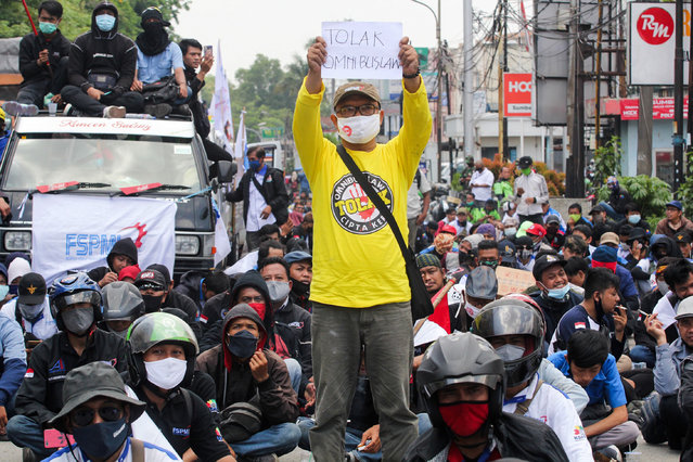 A worker holds a sign as he takes part in a rally with others against a government omnibus bill on job creation, which they believe will deprive workers of their rights, in Tangerang on October 5, 2020. (Photo by Fajrin Raharjo/AFP Photo)