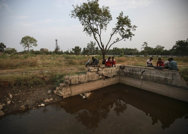 Residents sit atop a crumbling wall beside a pond near the abandoned former Union Carbide pesticide plant in Bhopal November 11, 2014. (Photo by Danish Siddiqui/Reuters)