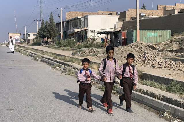 Afghan children walk along a road during the first day of their school's reopening in Kabul, Afghanistan, Saturday, August 22, 2020. Public and private schools in the country were reopened since the beginning of this year due to the coronavirus pandemic. (Photo by Rahmat Gul/AP Photo)