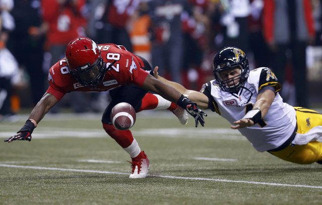 Calgary Stampeders' Brandon Smith (L) and Hamilton Tiger Cats' quarterback Zach Collaros chase a loose ball in the first half during the CFL's 102nd Grey Cup football championship in Vancouver, British Columbia, November 30, 2014. (Photo by Mark Blinch/Reuters)