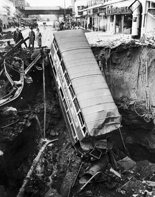 This unusual view of a bus nosed into a huge bomb crater in a London street, was made after one of last year's heavy night air raids of 1941. The omnibus seen in the crater in a London Suburban street  in photo released on January 23, 1942. (Photo by AP Photo)