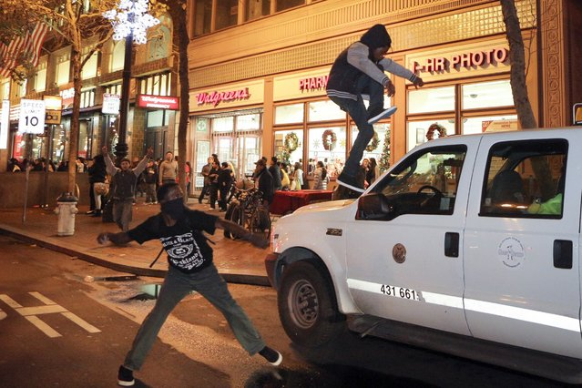Protesters try to smash the windshield of a truck during a demonstration against the grand jury decision in the Ferguson, Missouri shooting of Michael Brown in San Francisco, California November 28, 2014. (Photo by Elijah Nouvelage/Reuters)