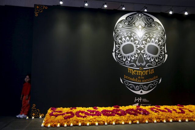 A child stands next to an altar for Day of the Dead in memory of Mexico's killed and disappeared journalists at the Memory and Tolerance Museum in Mexico City October 29, 2015. (Photo by Carlos Jasso/Reuters)