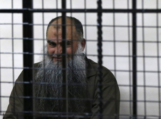 Radical Muslim cleric Abu Qatada smiles as he sits and waits behind bars before his acquittal at the State Security Court in Amman, in this September 24, 2014 file photo. (Photo by Muhammad Hamed/Reuters)