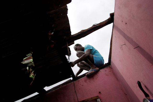 A man fixes the roof of a house damaged by Hurricane Matthew in Les Cayes, Haiti, October 5, 2016. (Photo by Andres Martinez Casares/Reuters)