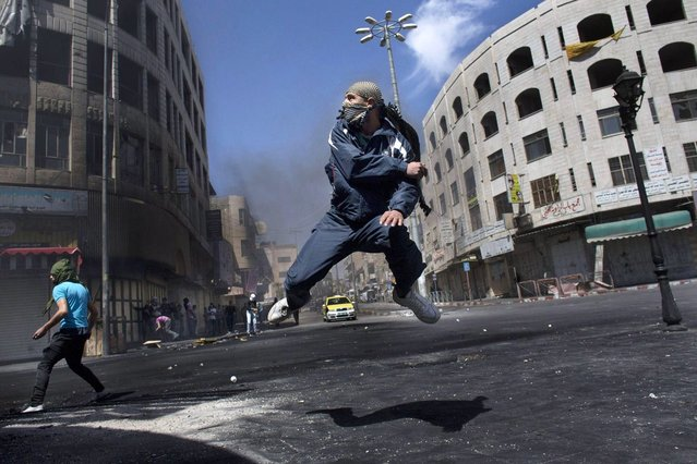 A Palestinian man throws a stone at Israeli forces during a riot in the West Bank city of Hebron Wednesday, April 3, 2013, the day after the death of Palestinian prisoner Maysara Abu Hamdiyeh at an Israeli jail. Palestinian prisoners have been rioting and hunger striking since 64-year-old Abu Hamdiyeh died of throat cancer on Tuesday. The Palestinians have blamed Israel for the man's death, saying he was not given proper medical care. Abu Hamdiyeh had been serving a life sentence for his role in a foiled attempt to bomb a busy cafe in Jerusalem in 2002. (Photo by Bernat Armangue/AP Photo)