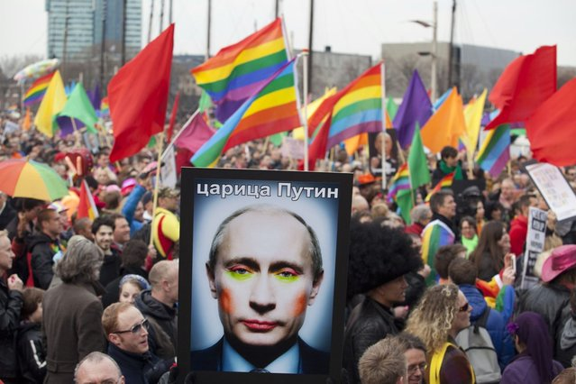 A demonstrator holds up a picture depicting Russian President Vladimir Putin with make-up, during a protest by the gay community in Amsterdam April 8, 2013. Russia does not discriminate against homosexuals, Putin told reporters in Amsterdam on Monday where he was greeted by gay rights and other activists critical of Russia's track record. Putin is on one-day visit in the Netherlands for the start of the Netherlands-Russia Year. (Photo by Cris Toala Olivares/Reuters)