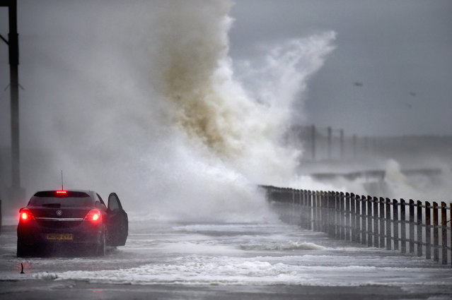 A car drives along Seaview road as waves crash over on December 9, 2014 in Saltcoats, Scotland. The Met Office has issued a yellow weather warning for the next forty eight hours as high winds start to build ahead of an Atlantic storm due tomorrow. (Photo by Jeff J. Mitchell/Getty Images)