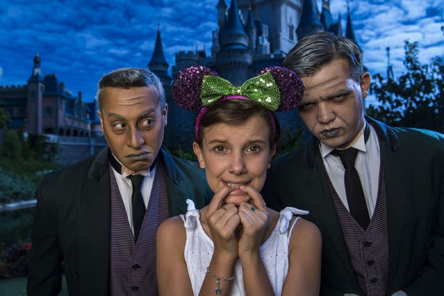 """In this handout photo provided by Disney Parks, Netflix's """"Stranger Things"""" star Millie Bobby Brown, known as """"Eleven"""", a girl with super powers against evil forces, poses with two """"grave diggers"""" at Magic Kingdom Park October 12, 2016 in Lake Buena Vista, Florida. Brown is currently vacationing with her family at Walt Disney World Resort. (Photo by Matt Stroshane/Disney Parks via Getty Images)"""