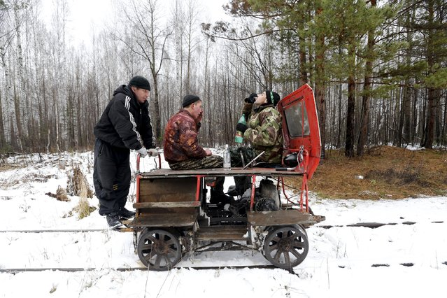 "(L-R) A man nicknamed ""Barcelona"", Alexey Bolotov and Alexey Jakushin drink vodka as they travel by a pioneer motorised railcar on their way to Kalach, Sverdlovsk region, Russia October 18, 2015. The ""pioneer,"" a light auxiliary rail vehicle, is a popular form of transport among people who live along the Alapayevsk railway. (Photo by Maxim Zmeyev/Reuters)"