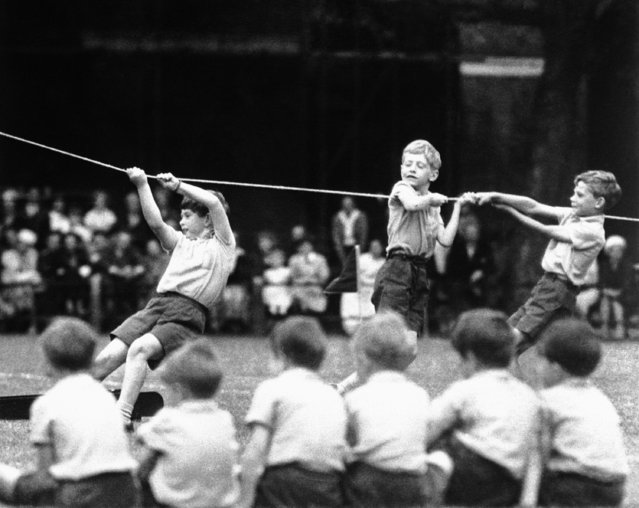 Prince Charles, eight-year-old heir to the British Throne, center, is just one of the boys during a sports day, at the private school he is attending near Buckingham Palace, July 8, 1957, London, England. He's an agile Prince as he swings across a simulated chasm on a steel bar. He's also a helpful Prince, giving school mates a hand to move a model of an 8-pound field gun across the breach. The Queen attended and watched her son participate also in foot race and cricket match. (Photo by AP Photo)