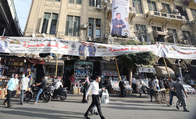 Egyptians walk past an array of election campaign banners ahead of parliamentary elections, in Cairo, Egypt, 04 November  2020. The first round of the second phase of the Parliamentary elections for citizens in Egypt is scheduled to be held on 07-08 November 2020 to elect the House of Representatives. (Photo by Khaled Elfiqi/EPA/EFE/Rex Features/Shutterstock)