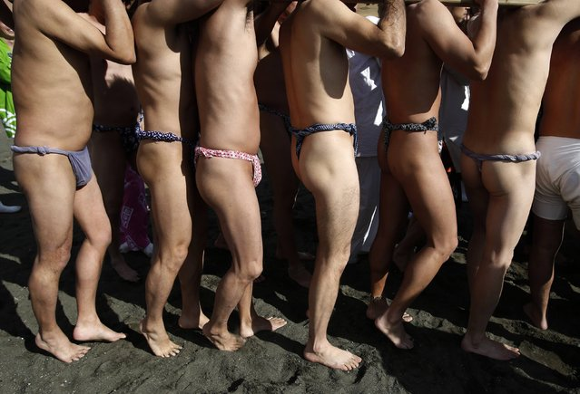 "Participants wearing the traditional ""fundoshi"" or loincloth carry a ""mikoshi"" or portable shrine as they carry it into the sea during a festival to wish for calm waters in the ocean and good fortune in the new year in Oiso, west of Tokyo, January 1, 2015. (Photo by Yuya Shino/Reuters)"