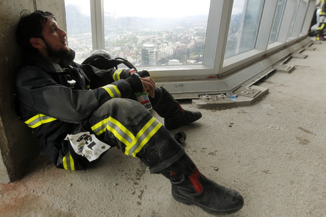 """A firefighter recovers after climbing the 1800 steps of the Costanera Centre Tower as part of the """"Race for Life"""" aimed at encouraging organ donation in Chile, in Santiago, on October 16, 2016. (Photo by Claudio Reyes/AFP Photo)"""