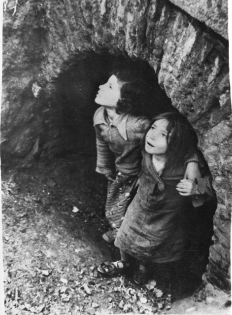Two young girls take refuge in the mouth of a sewer during a fascist raid in Madrid, Spain, February 8, 1937, during the Spanish Civil War. Weeks of such raids seem to have made them more interested than frightened of the falling bombs. (Photo by AP Photo)