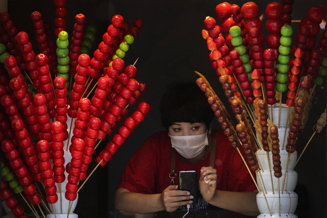 A vendor wearing a protective face mask looks out of her store selling sugar-coated haws on a stick in Beijing, Sunday, April 12, 2020. (Photo by Andy Wong/AP Photo)