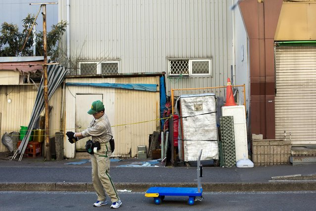 A worker practises a golf move as he waits for a delivery van in the outer part of the Tsukiji fish market, the Jogai Shijo, in Tokyo January 4, 2015. (Photo by Thomas Peter/Reuters)