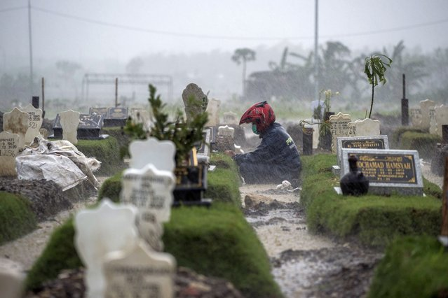 A man sits by the grave of a Covid-19 coronavirus victim amid pouring rain at Keputih cemetery in Surabaya, East Java, Indonesia on January 7, 2021. (Photo by Juni Kriswanto/AFP Photo)