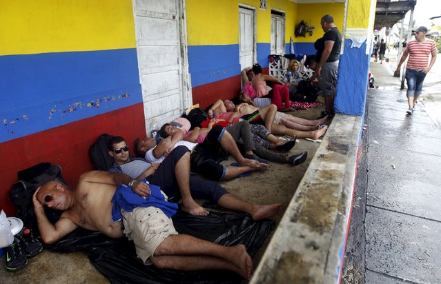 Cuban migrants sleep by the doorway of a house as they wait for their flight or boat ticket to continue their journey north, in Puerto Obaldia in the province of Guna Yala, Panama November 28, 2015. According to local media, some 900 Cubans have turned up at the jungle port seeking accommodation and a plane ride out of the area. But with only small planes capable of carrying some 17 people flying in and out of Puerto Obaldia, frustrations are running high amongst the migrants. (Photo by Carlos Jasso/Reuters)