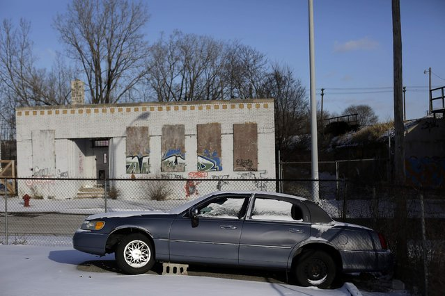 An older model Lincoln Town Car with a damaged wheel sits in a parking lot of a business in Detroit, Michigan January 7, 2015. (Photo by Joshua Lott/Reuters)