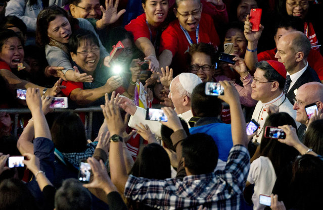 In this Friday, January 16, 2015 file photo, Pope Francis, center, followed by Cardinal Luis Antonio Tagle, waves as he arrives at the Mall of Asia arena, in Manila, Philippines, for a meeting with families. It's a scene that has repeated itself throughout Pope Francis' visit to the Philippines, from the sidewalks lining his motorcade routes to the hallowed nave of Manila's cathedral. (Photo by Alessandra Tarantino/AP Photo)
