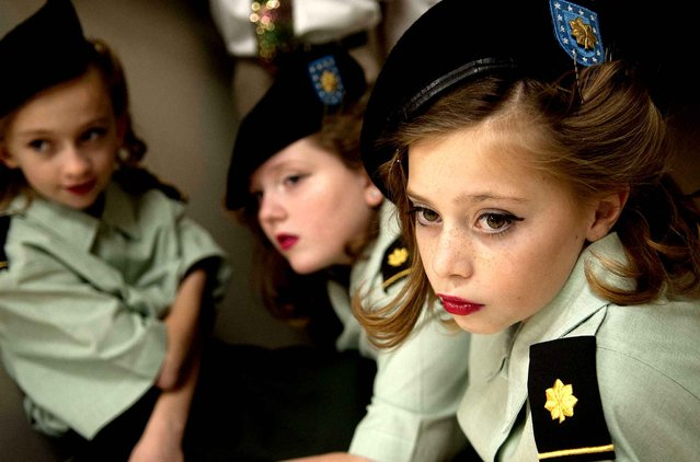 Winton Elementary fifth graders Juliana Ragan, from left, Chloe Windsor and Paisley Ganske wait backstage for their turn to perform as the Andrew Sisters during the Pearl Harbor/Veterans assembly at the school on Monday, December 7, 2015, in Coeur d'Alene, Idaho. Dec. 7 is the 74th anniversary of the Japanese bombing of Pearl Harbor. (Photo by Kathy Plonka/The Spokesman-Review via AP Photo)