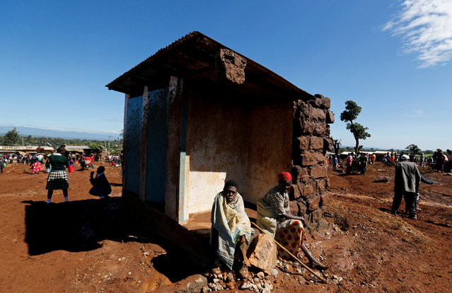 Survivors sit outside their destroyed house after a dam burst, which unleashed water at nearby homes, in Solio town near Nakuru, Kenya May 10, 2018. (Photo by Thomas Mukoya/Reuters)