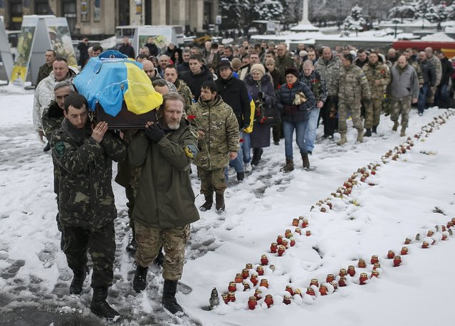 "Servicemen from the battalion ""Aydar"" carry a coffin bearing the body of their comrade Sergiy Nikonenko, who was killed in the fighting in Luhansk region in eastern Ukraine,during a funeral ceremony at the Independence Square in central Kiev, January 20, 2015. Pro-Russian separatists renewed attacks on Ukrainian forces at an airport complex in the east on Monday after Kiev launched a mass operation to reclaim lost ground there that Russia called a ""strategic mistake"". (Photo by Gleb Garanich/Reuters)"