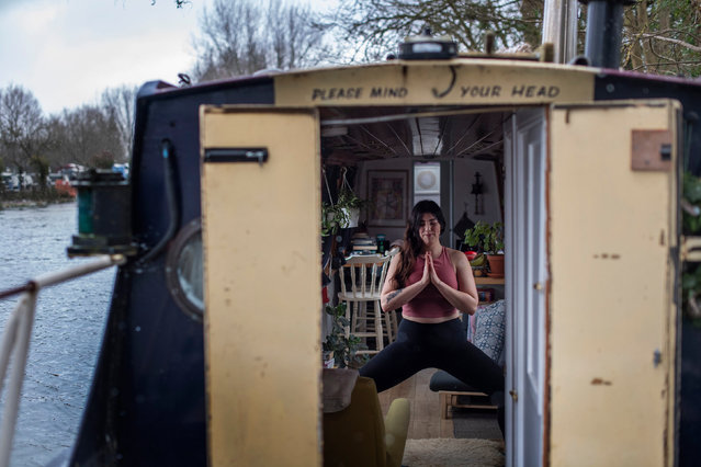"Yoga teacher Harriet McAtee, who is 6ft tall, performs a ""Utkata Konasana"" pose during a class on her 6ft wide narrowboat in Oxford, UK on Thursday February 18, 2021. The Coronavirus pandemic has forced Harriet to conduct her classes via zoom video calls rather than face-to-face as she did pre-pandemic, but she now teaches to people all around the world, with students reaching as far as New Zealand. (Photo by Victoria Jones/PA Images via Getty Images)"