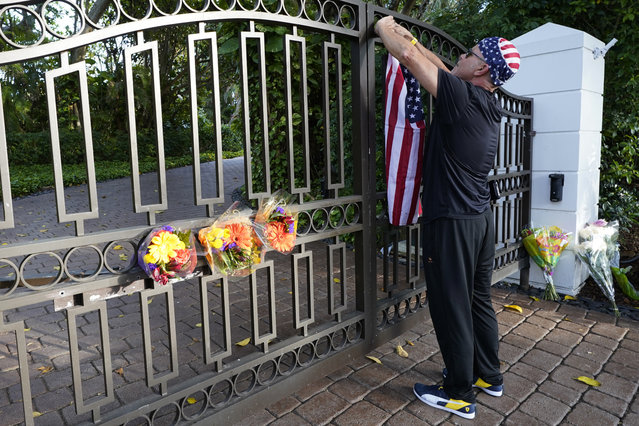John Hensel attaches an American flag to the gate of the home of his friend and talk radio host Rush Limbaugh, Wednesday, February 17, 2021, in Palm Beach, Fla. Limbaugh, 70, died this morning of lung cancer. (Photo by Marta Lavandier/AP Photo)