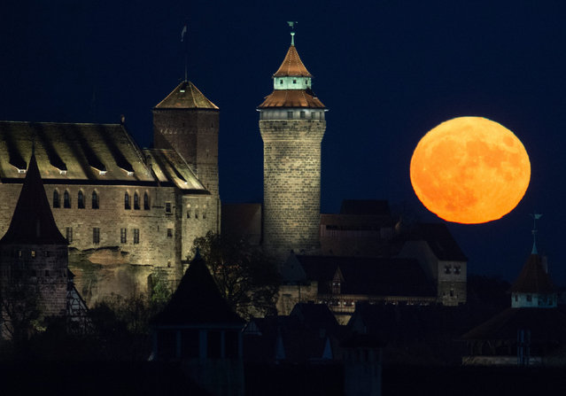 """The full moon rises behind the Kaiserburg castle in Nuremberg, Germany, 14 November 2016.The moon is the largest full moon since 1948 also known as the """"supermoon"""", when the moon reaches its closest point to Earth. The next time the moon will be this close will be on 25 November 2034. (Photo by Timm Schamberger/EPA)"""