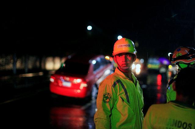 Comandos de Salvamento rescuer Emmanuel Martinez stands at the scene of a car accident in San Salvador, El Salvador July 7, 2016. (Photo by Jose Cabezas/Reuters)