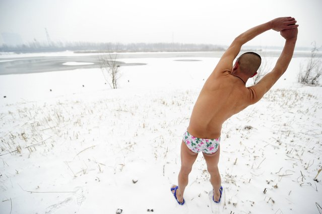 Winter swimmer Li Wenyan, 43, stretches before getting in a partially frozen river in Taiyuan, Shanxi province, January 24, 2015. (Photo by Reuters/Stringer)