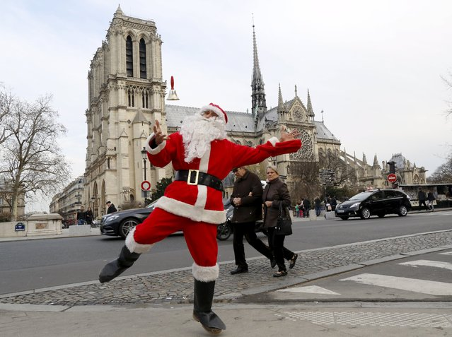 A man dressed as Santa Claus jumps near the Notre Dame Cathedral in Paris, France December 20, 2015. (Photo by Jacky Naegelen/Reuters)